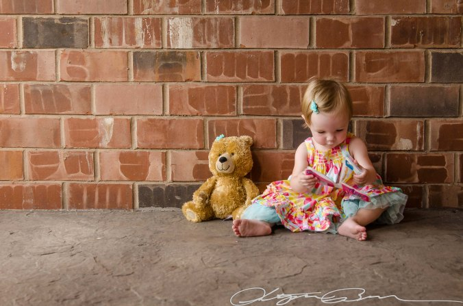 baby reading with teddy bear